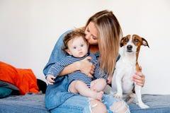 有小婴孩和狗的年轻母亲 库存图片