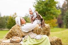有小婴孩的农民母亲在使用在领域的干草堆的夏天 免版税库存照片