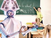 有小学生的老师机器人在黑板附近的学校课程的 免版税库存照片