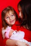 有小孩女儿和新出生的婴孩的母亲 库存图片