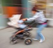 有小孩子和摇篮车的母亲步行沿着向下街道的 库存图片