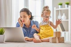 有小孩工作的母亲 免版税库存照片