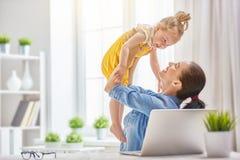 有小孩工作的母亲 免版税图库摄影