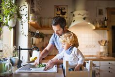 有小孩男孩烹调的年轻父亲 免版税库存图片