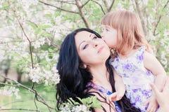 有小孩的母亲在春天庭院里 免版税图库摄影