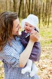 有小小女儿的年轻母亲在公园 库存图片
