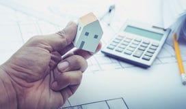 有小屋模型在手边和计划设计的建筑师 概念 免版税库存照片