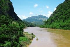 有小山山和豪华的云彩森林的热带河 免版税库存照片