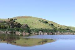 有小山的池塘在距离 库存照片