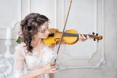 有小提琴的妇女在白色peignoir 被限制的 诱人 图库摄影