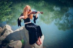有小提琴的农村红发女孩 免版税库存照片