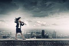 有小提琴的女实业家 免版税库存图片
