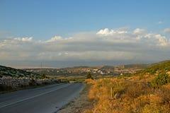 有小村庄的空的海岛路小山的 免版税库存照片