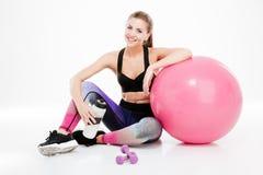 有小杠铃和桃红色球的年轻美丽的健身女孩 库存照片