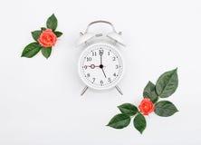 有小桃红色玫瑰的闹钟在上升了叶子 库存图片
