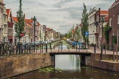 有小桥梁的沿途有树的长的运河,它的银行的砖房子和在荷兰扁圆形干酪的多云天 免版税库存照片
