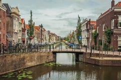 有小桥梁的沿途有树的长的运河,它的银行的砖房子和在荷兰扁圆形干酪的多云天 库存照片