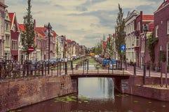 有小桥梁的长的运河,它的银行的砖房子和在荷兰扁圆形干酪的多云天 免版税库存图片