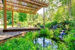 有小池塘和露台区域的美丽如画的后院农厂庭院 免版税库存图片