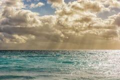 有小波浪的柔和的海和与光束的美丽的多云天空 免版税库存图片
