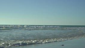 有小波浪的风平浪静,明白蓝天 起波纹在沙子的波浪 洗涤光滑的白色的美丽的海浪泡沫 股票录像