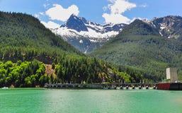 有小瀑布山脉围拢的水坝的湖 库存照片
