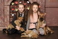 有小狗的两个姐妹女孩 免版税库存图片