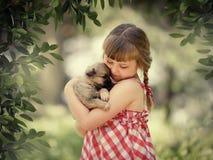 有小狗的小女孩 免版税库存图片