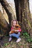 有小狮子狗的女婴坐草 免版税库存图片