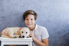 有小猎犬狗的逗人喜爱的青少年的男孩在屋子里 免版税库存图片