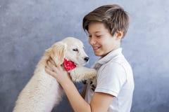 有小猎犬狗的逗人喜爱的青少年的男孩在屋子里 免版税库存照片