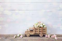有小玫瑰的木玩具卡车在白色的后面开花 免版税库存图片