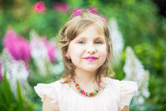 有小珠项链的十几岁的女孩在她的脖子,在她的嘴唇的一支紫色唇膏上反对绿色叶子背景  免版税图库摄影