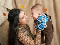 有小男孩的秋天妇女黄色秋天叶子的、苹果、南瓜和装饰在纺织品,愉快的家庭和国家概念 库存照片