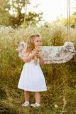有小白肤金发的女孩的怀孕的美丽的母亲在摇摆附近的一件白色礼服的,笑,童年,放松 免版税库存照片