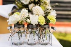 有小白色和绿色花束的瓶子 库存照片