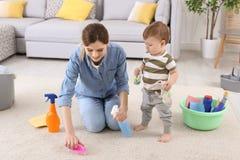 有小的儿子清洁地毯的主妇 免版税库存照片