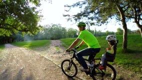 有小的儿子骑马自行车的父亲以绿色 股票视频
