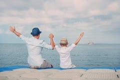 有小的儿子致敬的父亲在海天线线的一艘船 免版税库存照片
