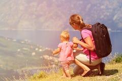 有小的女儿旅行的母亲在山 免版税库存图片