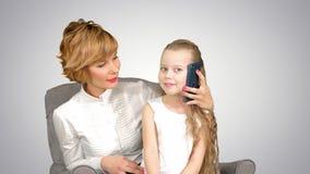 有小的女儿电话,在她的母亲附近坐白色背景 免版税库存图片