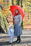 有小的女儿立场的少妇在一把红色伞下在秋天公园 免版税库存图片