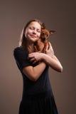 有小的小狗的俏丽的少年女孩 免版税库存照片