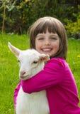 有小的山羊的小女孩 免版税库存图片