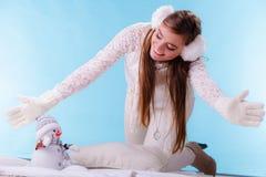 有小的雪人的逗人喜爱的妇女 背景美丽的方式女孩查出的空白冬天 库存图片