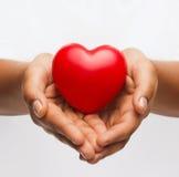 有小红色心脏的女性手 免版税库存图片