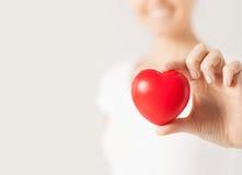 有小红色心脏的愉快的妇女 免版税库存图片