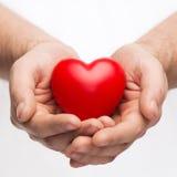 有小红色心脏的男性手 免版税库存图片