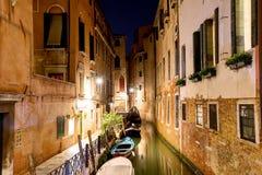 有小船和一座小桥梁的运河在威尼斯在晚上,意大利 威尼斯明信片 免版税库存照片