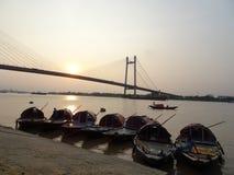 有小船的加尔各答Vidyasagar Setu桥梁在日落期间 免版税库存照片